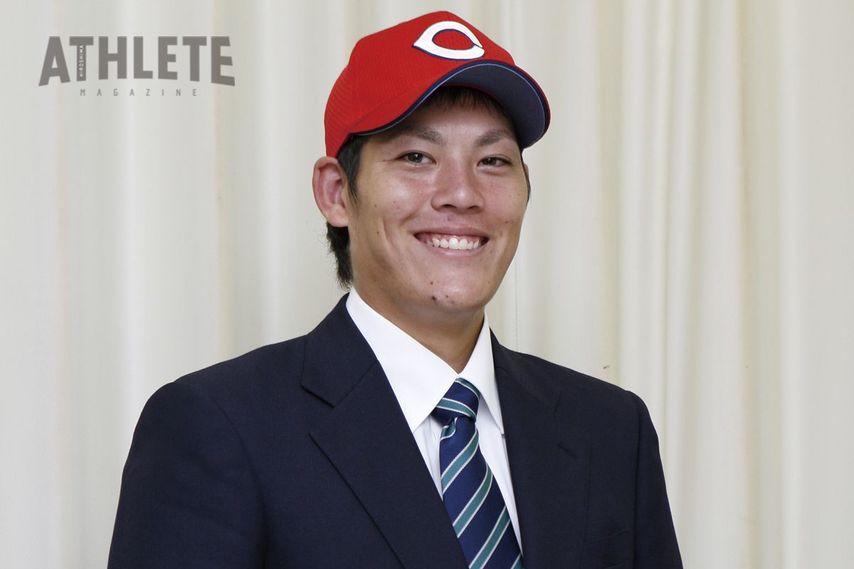 "<div class=""caption"">ドラフト指名直後、カーブ帽を被り笑顔を見せる九里亜蓮投手。</div>"